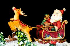 Father Christmas in his sleigh. Ceramic Father Christmas in his sleigh with reindeer on a black background Royalty Free Stock Image
