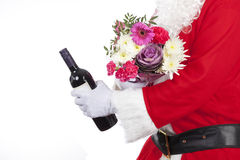 Father christmas offering a bunch of fresh flowers and a bottle of wine Stock Photos