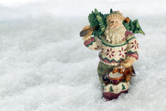 Father Christmas Old Fashioned in Snow. Father Christmas vintage handmade decoration against a snow backdrop with copy space Stock Images
