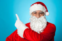 Father Christmas pointing away, copy space area Royalty Free Stock Images