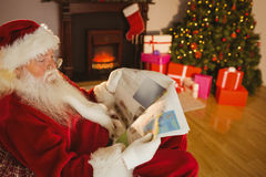 Father christmas reading newspaper on the couch Stock Images