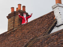 Father Christmas on roof top. Cookham, UK - December 7 2014: Santa Claus seen on old rooftop at Cookham Christmas street market Stock Photo