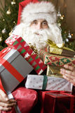 Father Christmas/Santa Claus holding a pile of presents Royalty Free Stock Images