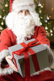 Father Christmas/Santa Claus holding a present Stock Photo