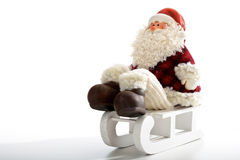 Father Christmas sitting on sledge   on white Royalty Free Stock Photography
