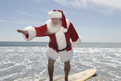 Father Christmas Surfboards At The Water's Edge royalty free stock image