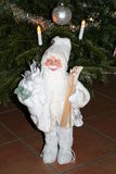 Father Christmas in white dress. Smiling Father Christmas  is standing in front of Christmas tree with parcels for children Royalty Free Stock Photography