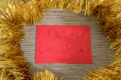 Father christmas write on a red paper with decorations stock photos
