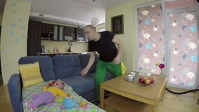 Father clean floor with hoover and worried baby cry on sofa. 4K stock footage