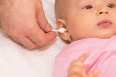 Father cleaning baby's ear Stock Images