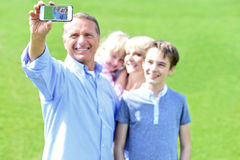 Father clicking family selfie, outdoors. Royalty Free Stock Images