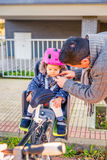 Father closing helmet to her daughter sitting in Royalty Free Stock Photo