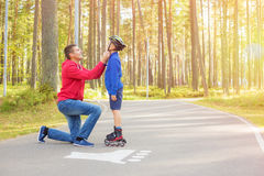 Father closing his sons helmet Royalty Free Stock Image