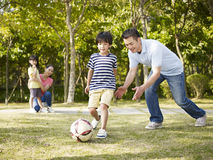 Father coaching son to play soccer. Asian father teaching son to play soccer (football) in a park while mother and daughter watching from behind Royalty Free Stock Photos