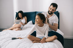 Father combing hair of daughter while mother using digital tablet in bedroom royalty free stock photo