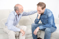 Father comforting elderly son Royalty Free Stock Photo