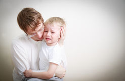 Father comforting her crying little son Royalty Free Stock Image