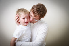 Father comforting her crying little son Royalty Free Stock Photography