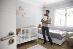 Father Comforting Newborn Baby Son In Nursery Stock Photography