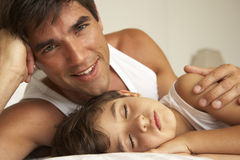 Father Comforting Sleeping Son In Bed Stock Image