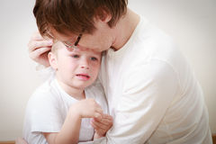 Father comforting son in tears. Father comforting her crying little son - parenthood concept Stock Photos