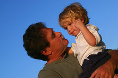 Father comforting young son. Father holding young boy in his arms against a blue sky Royalty Free Stock Photos