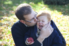 Father comforts son. Dad kisses and gives comfort to crying child Stock Image