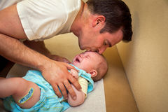Father Comforts Vaccinated Son. A father tries to comfort his 2 month old son with a kiss after the boy received his vaccination shots Royalty Free Stock Image