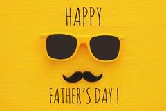 Father& x27; concetto di giorno di s Occhiali da sole gialli dei pantaloni a vita bassa e baffi divertenti fotografie stock