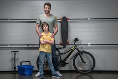 Father and confident son standing in workshop with bicycle and skateboard Royalty Free Stock Photos