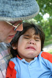 Father consoling crying toddler. Father consoling his crying toddler stock photo
