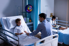 Father consoling his son during visit in ward. At hospital Stock Photo