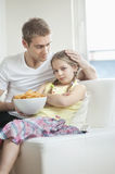 Father convincing daughter to eat wheel shape snack pellets Stock Images