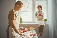 Father cooking for family with joy. Side view profile of adult standing at desk and rolling out dough. Boy drinking on windowsill. Focus on man Royalty Free Stock Image