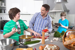 Father cooking with his children in the kitchen - family life Stock Photography