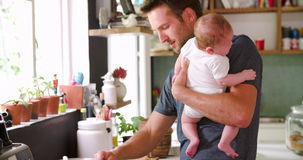 Father Cooking Meal Whilst Holding Baby In Kitchen. Man cooking lunch at stove whilst holding baby daughter.Shot on Sony FS700 at frame rate of 25fps stock footage