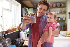 Father Cooks Meal Whilst Holding Young Daughter Royalty Free Stock Photography