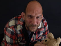 Father Cries. An older balding male holds a teddy bear, tears running down his face Royalty Free Stock Image
