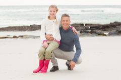Father crouching with daughter sitting on his knee. At the beach Stock Image