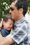 Father with crying child. Father holding, hugging and comforting  his upset hurt crying son child Stock Photography