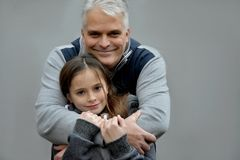 Feeling of security. Father cuddles his sweet teenage daughter and gives her a feeling of security Stock Images