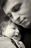 Father cuddling baby son. Black and white portrait of father cuddling baby son Royalty Free Stock Image