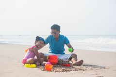 Father And cute asian daughter made a sand castle with toys on t