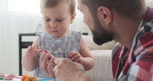 Father and baby daughter playing with plasticine. Father and cute baby daughter making shapes using plasticine stock footage