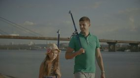 Father with cute daughter carrying fishing rods. Handsome millennial father and lovely elementary age daughter carrying fishing rods on shoulders and talking stock video footage