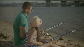 Father and cute girl fishing from shore on river. Positive father and cute elementary age daughter with fishing rods sitting on the sand talking and fishing stock video