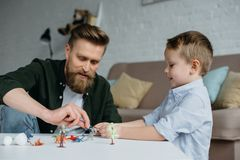 father and cute little son playing with various toy dinosaurs together