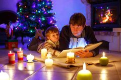 Father and cute little toddler boy reading book by chimney, candles and fireplace. Father and cute little toddler boyreading book by chimney, candles and stock images