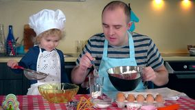 Father with cute toddler girl preparing cake in kitchen stock footage