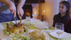Father cuts a festive fried chicken at the christmas table. Man holds a wooden fork and knife and cuts a delicious fried chicken. Two little daughters and mother stock footage